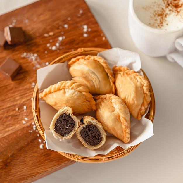 Czekolada Wewnątrz Puff Pestry I Filiżanka Kawy Na Drewnianej Desce Do Krojenia I Składników Premium Zdjęcia