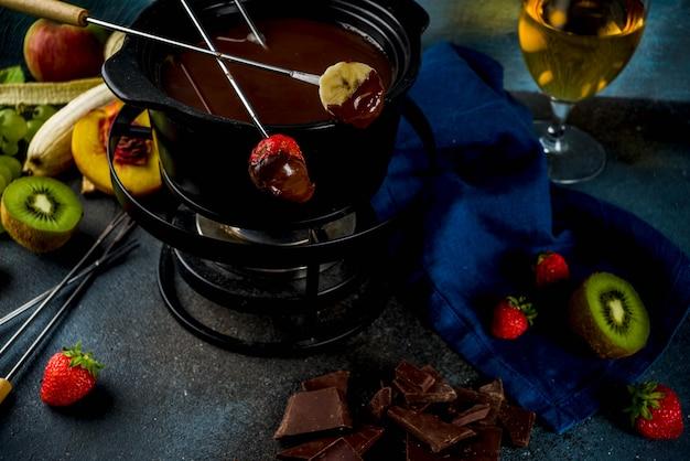 Czekoladowe Fondue W Tradycyjnym Garnku Do Fondue, Z Widelcami, Białym Winem, Różnorodnymi Jagodami I Owocami Premium Zdjęcia
