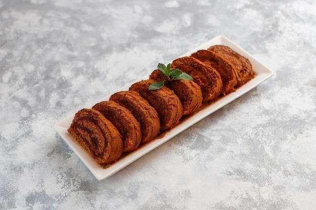 Czekoladowego torta rolka z kakaowym proszkiem na bielu talerzu, odgórny widok Darmowe Zdjęcia