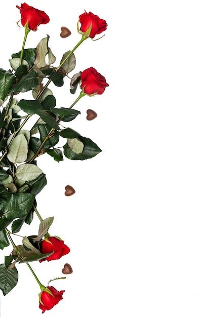 Czekoladowy cukierek i czerwone róże odizolowywający z copyspace. romantyczne walentynki. cukierki w kształcie serca z płaskimi kwiatami Premium Zdjęcia