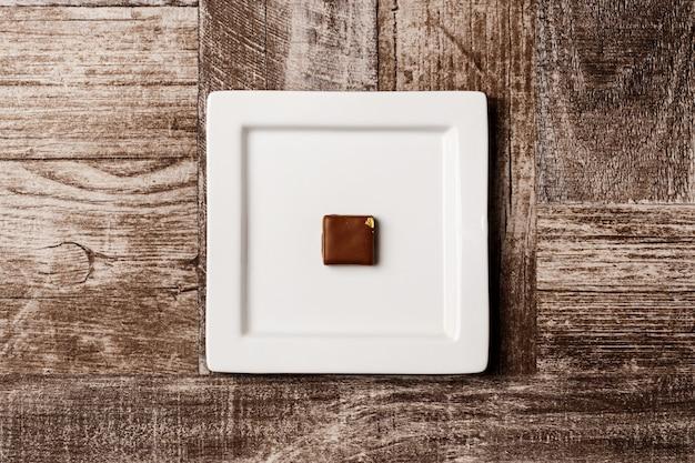 Czekoladowy Cukierek Na Bielu Talerzu Na Drewnianym Darmowe Zdjęcia