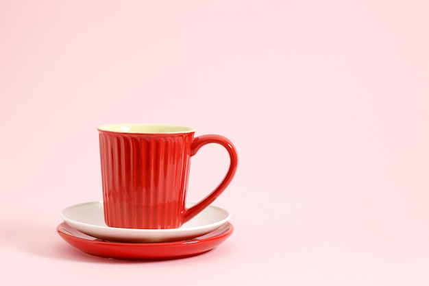 Czerwona filiżanka na pastelowych białych i czerwonych płytkach na różowym tle. Premium Zdjęcia