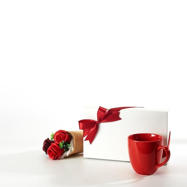 Czerwona Filiżanka Z Prezenta Pudełkiem I Różami Na Bielu Premium Zdjęcia
