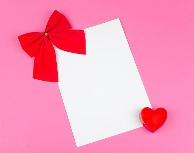 Czerwona kokarda i biała karta Premium Zdjęcia