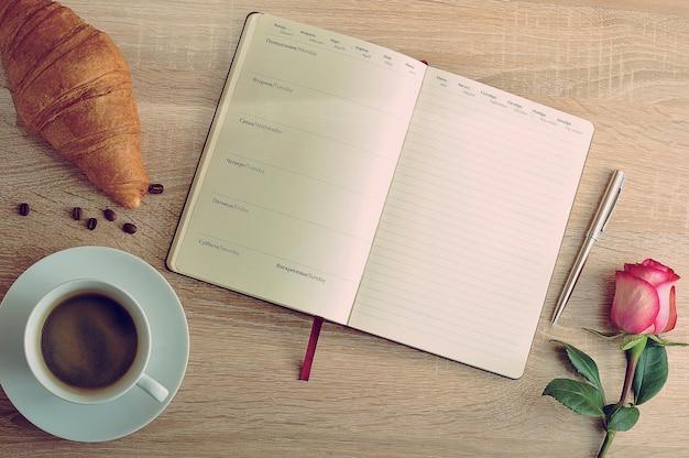 Czerwona róża i filiżanka kawy z rogalikiem i pamiętnik z dniami tygodnia Premium Zdjęcia