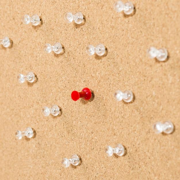 Czerwona Szpilka Otoczona Białymi Szpilkami Na Drewnianej Desce Darmowe Zdjęcia