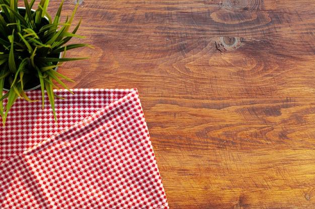 Czerwona W Kratkę Pielucha Lub Tablecloth Na Drewnianym Stole, Kopii Przestrzeń Premium Zdjęcia