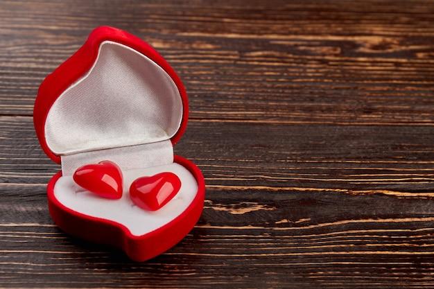 Czerwone Aksamitne Pudełko Z Kolczykami W Kształcie Serca. Pudełko W Kształcie Serca Z Dwoma Małymi Serduszkami I Miejscem Na Kopię. Szczęśliwych Walentynek. Premium Zdjęcia
