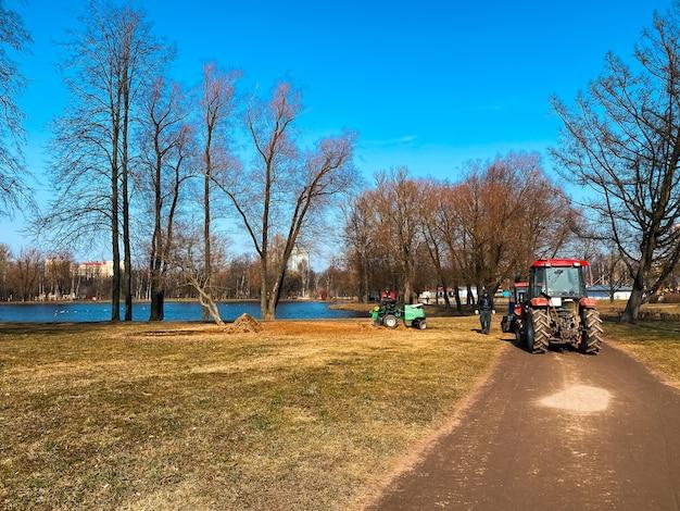 Czerwone Ciągniki Ciężarówki W Parku Miejskim Wiosna. Czyszczenie. Wczesna Wiosna. Pracuje. Słoneczny Wiosenny Dzień. Premium Zdjęcia