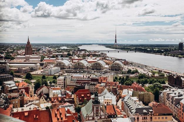 Czerwone Dachy Starej Rygi. Riga Gród W Słoneczny Letni Dzień. Widok Z Lotu Ptaka Na Stare Miasto Z Katedry W Kopule I Dźwiny W Rydze, łotwa Premium Zdjęcia