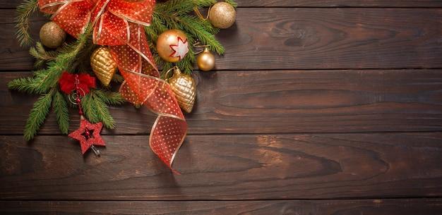 Czerwone I Złote świąteczne Dekoracje Z Płonącą świecą Na Powierzchni Drewnianych Premium Zdjęcia