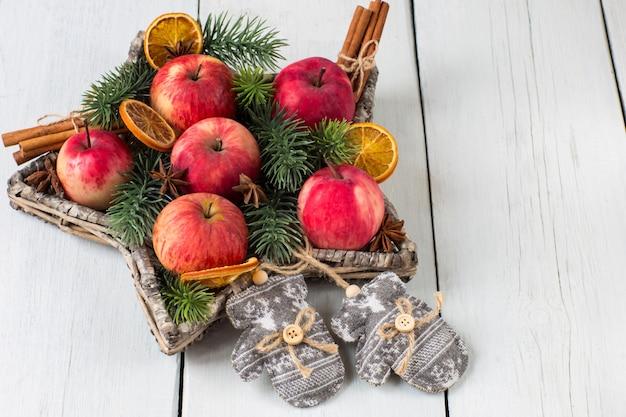 Czerwone Jabłka, Cynamon, Gałęzie Sosny I Rękawiczki Z Dzianiny Premium Zdjęcia