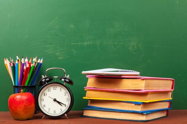Czerwone jabłko na stosie książek, papieru i ołówka na biurku Premium Zdjęcia