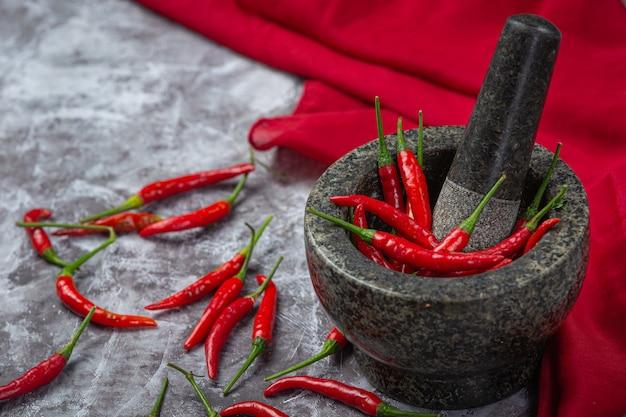 Czerwone Papryczki Chilli Są W Kamiennym Moździerzu Na Czarnej Powierzchni. Darmowe Zdjęcia