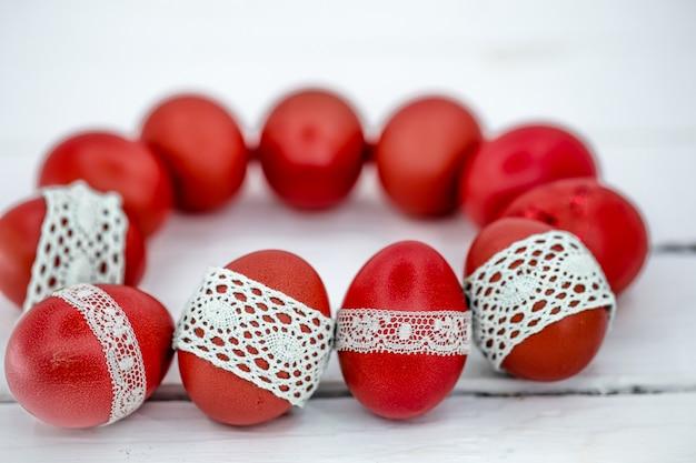 Czerwone Pisanki Na Białej Taśmie Koronki Wiązanej, Zbliżenie, Leżące Na Białym Drewnie Darmowe Zdjęcia