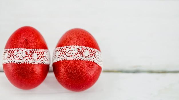 Czerwone Pisanki Na Białym Przewiązane Koronkową Wstążką, Zbliżenie, Leżące Na Białym Drewnie Darmowe Zdjęcia