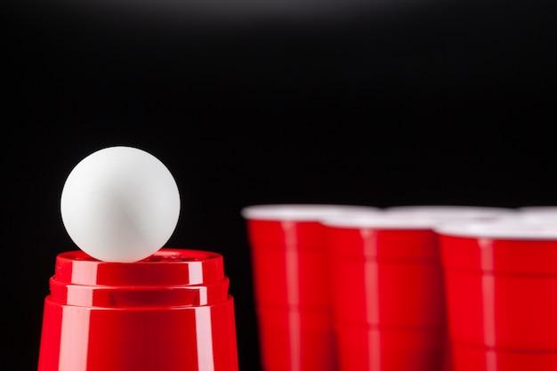 Czerwone plastikowe kubki i piłka do gry w piwnego ponga Premium Zdjęcia