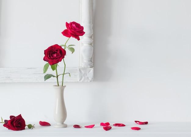 Czerwone Róże W Wazonie Na Przestrzeni Białej ścianie Premium Zdjęcia