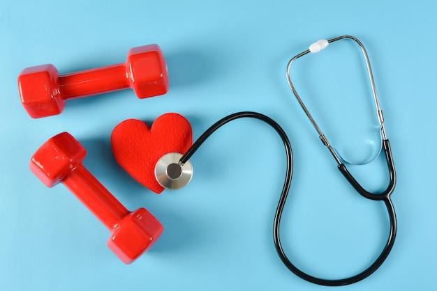 Czerwone serca, stetoskop i czerwone hantle. światowy dzień zdrowia, pojęcie opieki zdrowotnej i medycznej, pojęcie ubezpieczenia zdrowotnego. Premium Zdjęcia