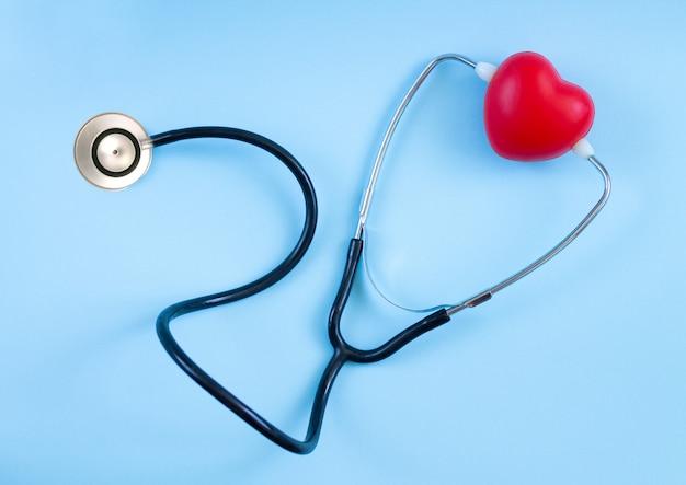 Czerwone Serce I Widok Z Góry Stetoskop Na Niebieskim Tle. Słuchanie Koncepcji Bicia Serca Premium Zdjęcia