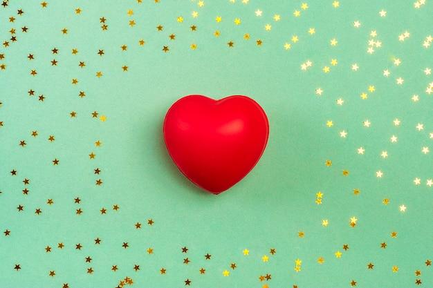 Czerwone serce i złote cekiny, leżał płasko widok z góry Premium Zdjęcia
