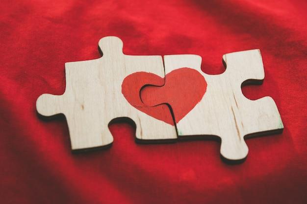 Czerwone serce jest narysowane na kawałkach drewnianej układanki leżących obok siebie na czerwonym tle. Premium Zdjęcia