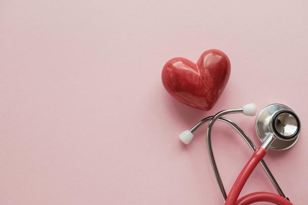 Czerwone Serce Z Stetoskopem Na Różowym Tle Premium Zdjęcia