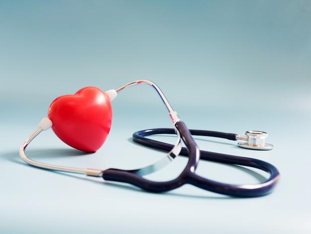 Czerwone Serce Za Pomocą Głęboko Niebieski Stetoskop Na Niebieskim Tle Premium Zdjęcia