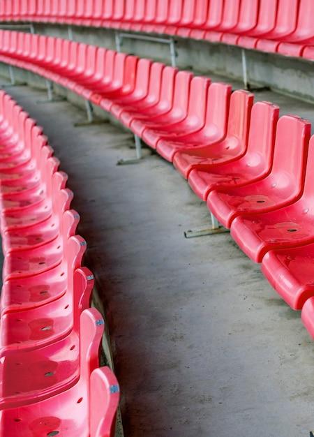 Czerwone Siedzenia Stadionowe Po Deszczu. Trybuna Piłkarska, Piłkarska Lub Stadion Baseballowy Bez Fanów Premium Zdjęcia
