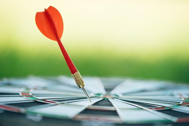 Czerwone strzałki strzałki uderzając w centrum tarczy z zielonym tle przyrody. Premium Zdjęcia