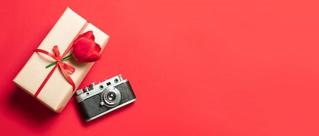 Czerwone Tulipany, Pudełko I Aparat Na Czerwonym Tle. Leżał Płasko, Widok Z Góry, Miejsce Na Kopię Premium Zdjęcia