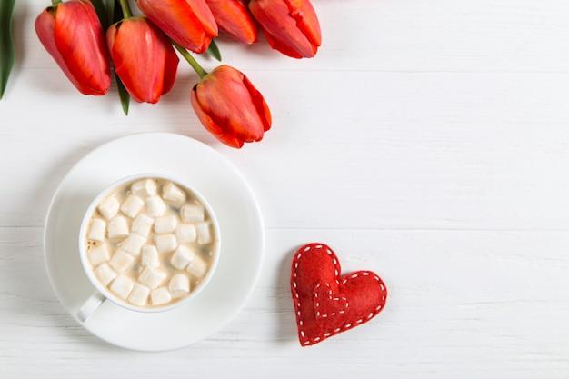 Czerwone Tulipany, Serce I Filiżankę Kawy Na Białym Stole. Poranny Prezent Na Wiosenne Wakacje, Dzień Matki. Skopiuj Miejsce Premium Zdjęcia