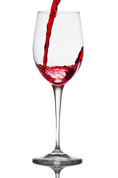 Czerwone Wino Wlewa Się Do Szklanki Na Białym Tle Na Białej ścianie Darmowe Zdjęcia