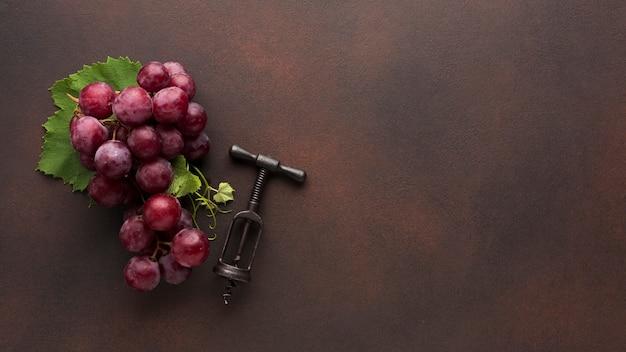Czerwone winogrona i korkociąg do wina Darmowe Zdjęcia