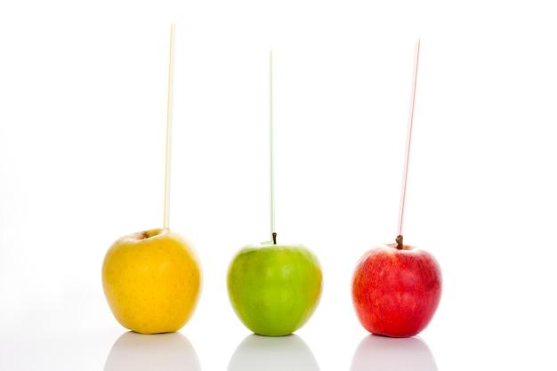 Czerwone, żółte I Zielone Jabłka Ze Słomkami Na Białym Tle Premium Zdjęcia