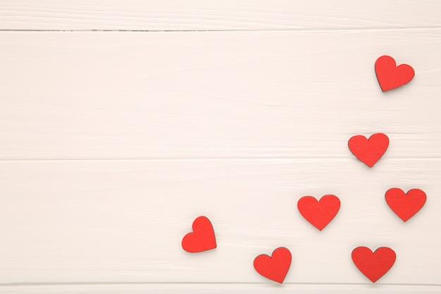 Czerwoni drewniani serca na drewnianym tle Premium Zdjęcia
