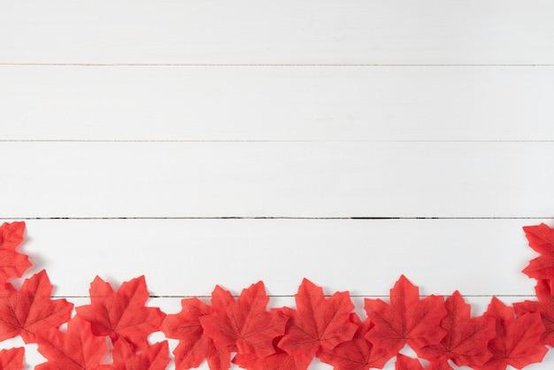 Czerwoni liście klonowi na białym drewnianym tle. jesień, jesień, widok z góry, miejsce. Premium Zdjęcia