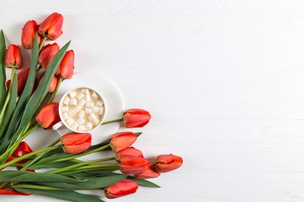 Czerwoni Tulipany I Filiżanka Kawy Z Marshmallows Na Bielu. Przygotowanie Pocztówki Na Wiosenne Wakacje. Skopiuj Miejsce Premium Zdjęcia