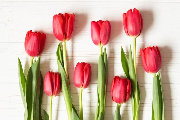 Czerwoni Tulipany Na Białym Drewnianym Stole. Leżał Płasko. Widok Z Góry. Premium Zdjęcia