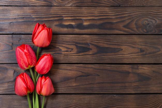 Czerwoni Tulipany Na Ciemnym Drewnianym Stole Premium Zdjęcia
