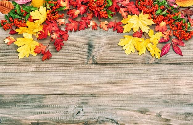Czerwoni żółci liście na drewnianym tle. jesień Premium Zdjęcia