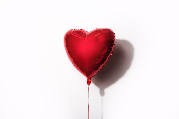 Czerwony Balonik W Formie Serca Na Białym Tle. Premium Zdjęcia