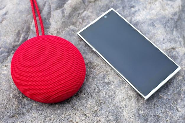 Czerwony Bezprzewodowy Przenośny Głośnik I Smartfon Leżący Na Kamieniu. Premium Zdjęcia