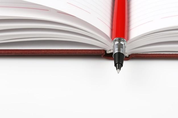 Czerwony Długopis Leżący Na Otwartym Notatniku Premium Zdjęcia