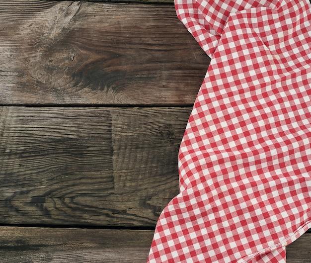Czerwony I Biały Tekstylny Ręcznik Kuchenny Na Drewnianej Powierzchni Premium Zdjęcia