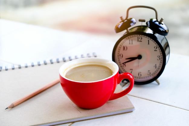 Czerwony Kubek Kawy Jest Połączony Z Czarnym Zegarem, Z Książkami I Premium Zdjęcia