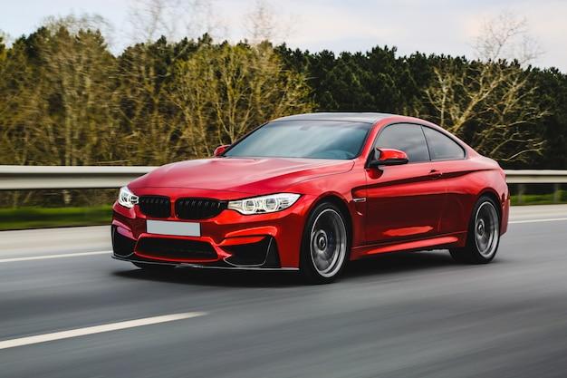 Czerwony luksusowy sedan na drodze. Darmowe Zdjęcia