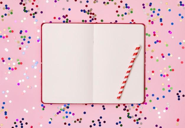 Czerwony notatnik z kolorowymi konfetti na różowym tle. leżał płasko, widok z góry Premium Zdjęcia