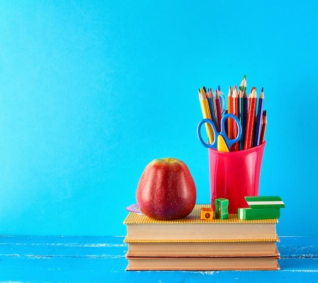 Czerwony Plastikowy Kubek Z Wielobarwnymi Drewnianymi Ołówkami Stoi Na Stosie Książek Premium Zdjęcia