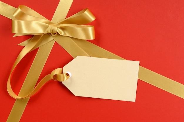 Czerwony Prezent, Złota Wstążka łuk, Pusta Etykieta Prezent Lub Etykieta, Miejsce Premium Zdjęcia